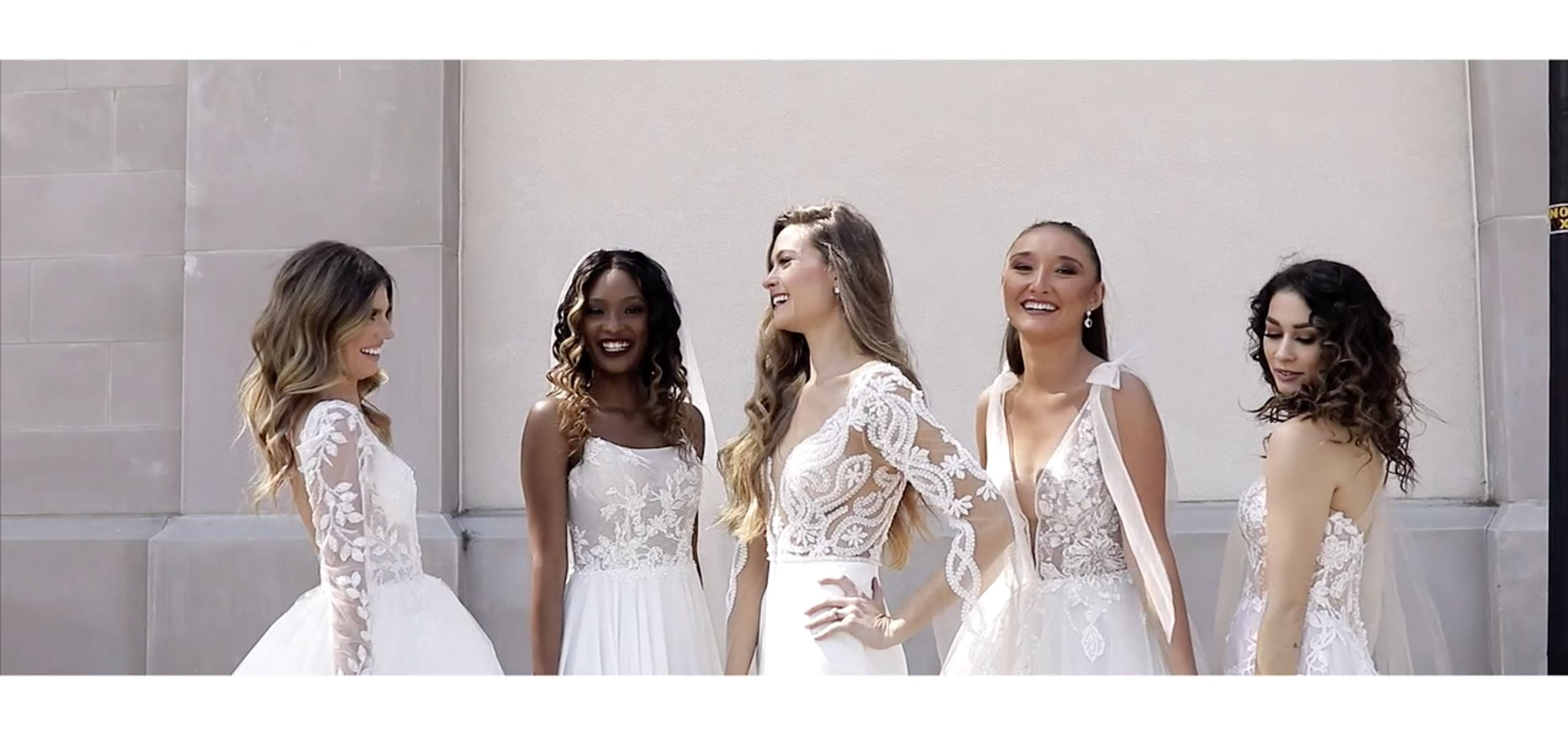 Five brides wearing floral white wedding dresses
